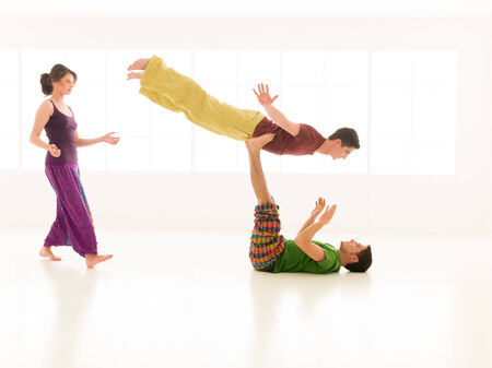 Three young people a woman and two men practice yoga partner in class on background window  photo
