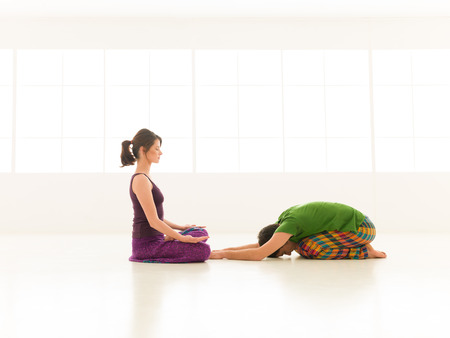 two people a man and a woman doing yoga partners in a white gym photo