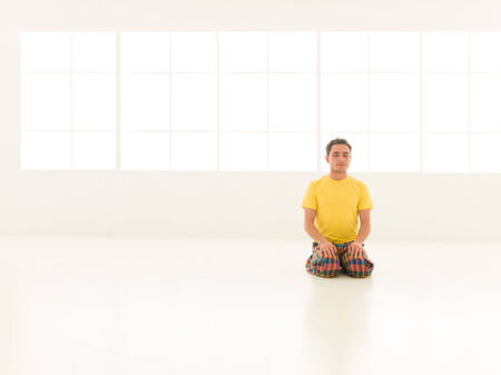 yoga studio: young man preparing for yoga lessons in gym vibrant color Stock Photo