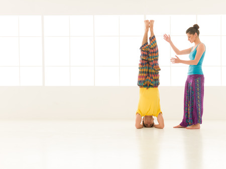 beautiful woman instructor with a handsome man dressed in vibrant colors are partners yoga in white gym photo
