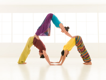 people dressed in vibrant colors perform yoga moves photo