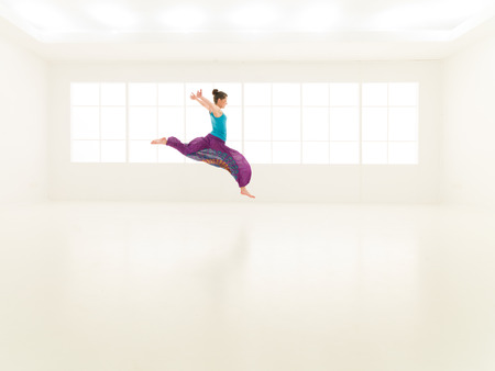 dance studio: Beautiful woman with multicolored pants and blue shirt jumping in room Stock Photo