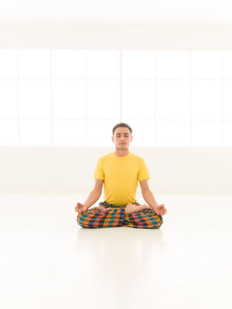 Young man doing yoga in white window studio lotus position photo
