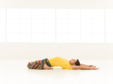 Colorful dressed male repeating supta virasana yoga exercises in a white room with window background