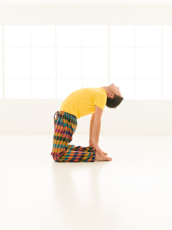 Colorful dressed male repeating ustrasana yoga exercises in a white room with window background photo