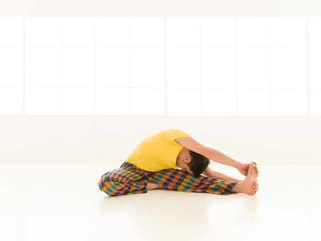 shirshasana: Colorful dressed male repeating Parivrtta Janu Sirsasana II  yoga exercises in a white room with window background