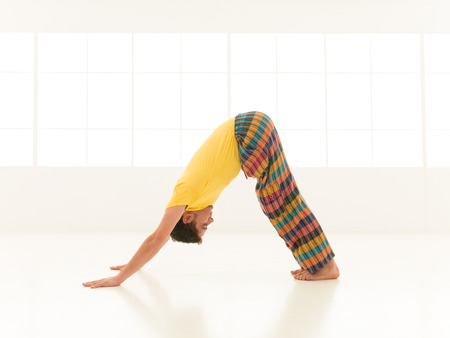 Colorful dressed male repeating Downward Facing Dog Ardho Mukha Svanasana yoga exercises in a white room with window background photo