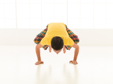 Colorful dressed male repeating bakasana yoga exercises in a white room with window background photo