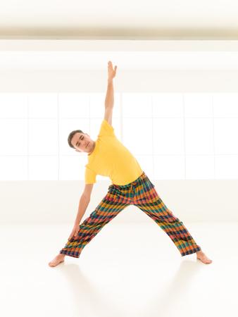 trikonasana: Colorful dressed male repeating Trikonasana yoga exercises in a white room with window background