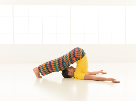 Colorful dressed male repeating Halasana yoga exercises in a white room with window background photo