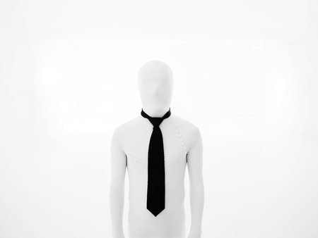 faceless white businessman standing straight, wearing a black tie photo