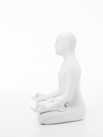 swadhisthana: faceless man dressed in white sitting in yoga lotus position Stock Photo