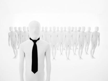 piramide humana: galán vestido de blanco con corbata negro, con maniquíes blancos dispuestos en varias filas