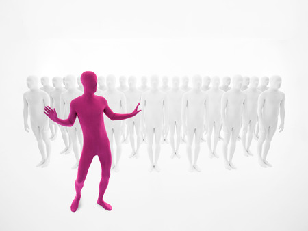 extra terrestrial: man dressed in pink dancing in front of a crowd of people dressed in white  Stock Photo