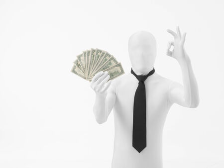 faceless man dressed in white with black tie makes an ok symbol, holding money arranged like a hand fan photo