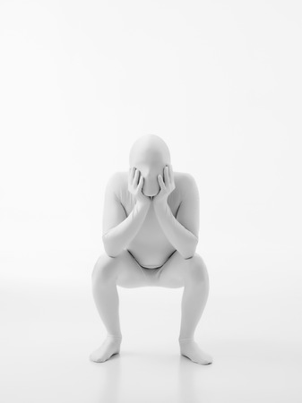 faceless man dressed in white with hands on his cheeks sits in a seat position photo