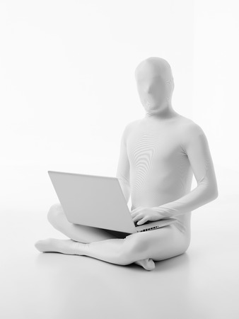 faceless man dressed white sitting with a laptop in lap typing