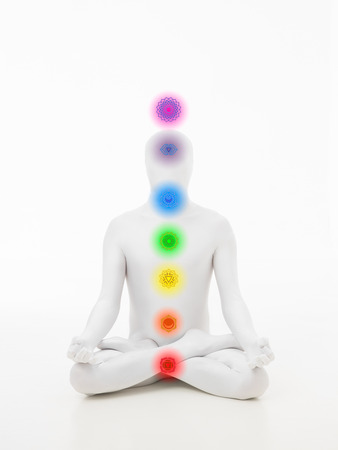 faceless man dressed in white sitting in yoga lotus position with chakra colored graphics Stock Photo - 28075842