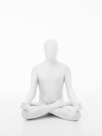 karmic: faceless man dressed in white sitting in yoga lotus position, front view