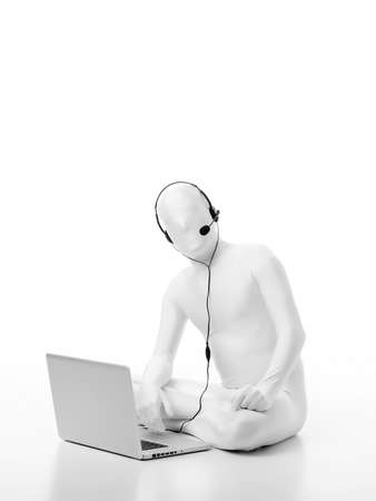 faceless man dressed in white sitting on the floor with a laptop and headphones microphone head standby  photo