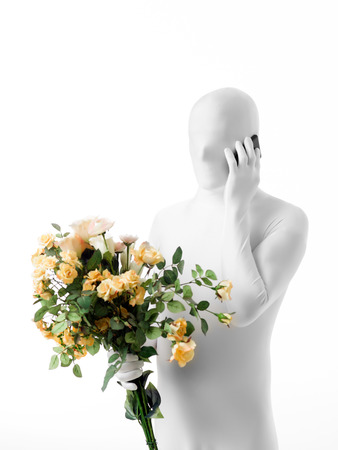 faceless man dressed  white with a bouquet of roses in hand talking on the phone photo