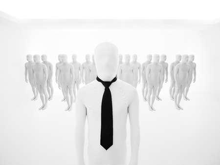 leading man dressed in white with black tie and background of aligned people photo