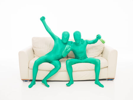 two faceless green men on the couch with a bottle of drink in hand on white  Stock Photo