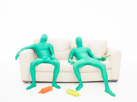Two green men faceless, tired, sitting on a couch with bottles of drink in hand on white background photo
