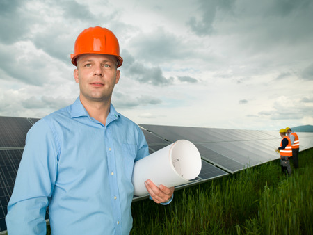 male engineer standing in solar panel station, holding blueprints, with two other workers in background photo