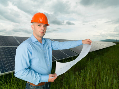 environmental issues: male engineer standing in solar panel station, holding blueprints Stock Photo