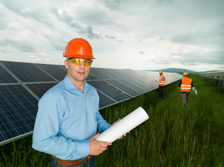 environmental issue: male engineer wearing protection equipment, standing in solar panel station, holding blueprints, with two other workers in background Stock Photo