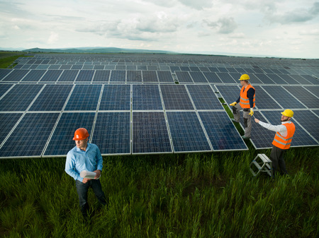 energy work: top view of three men wearing protection equipment inspecting solar panel station, outdoors
