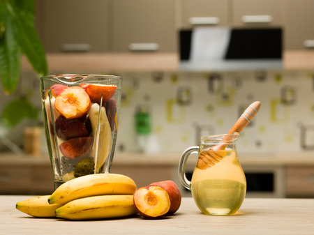 close-up of healthy colorful fruits, honey and tall blender cup with peaches and bananas on kitchen table photo