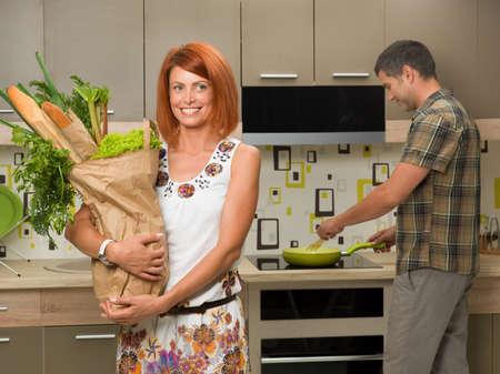 front view of beautiful woman smiling and holding shopping bag with groceries, in kitchen, with man in background cooking photo