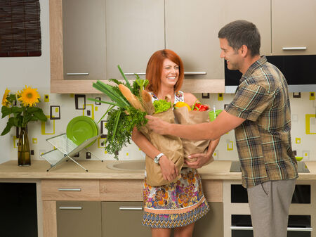 beautiful woman laughing and holding shopping bag with groceries, in kitchen, with a man smiling and trying to help her photo