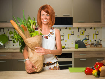 front view of young caucasian woman standing in a kitchen and holding paper bag with groceries, smiling photo