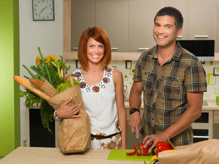 front view of happy couple in kitchen, woman holding paper bag with groceries standing next to a man chopping red pepper and smiling photo