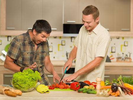 cut off: two handsome caucasian men in kitchen, pretending to cut ones finger off