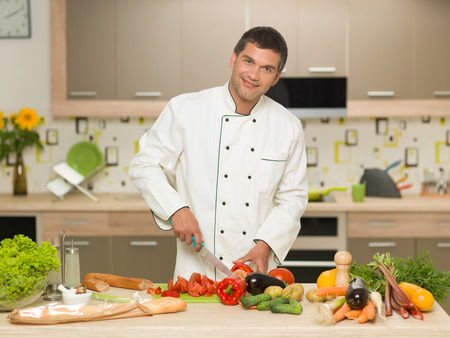 cutting vegetables: front view of caucasian man wearing chef clothing, cutting vegetables in kitchen, smiling Stock Photo
