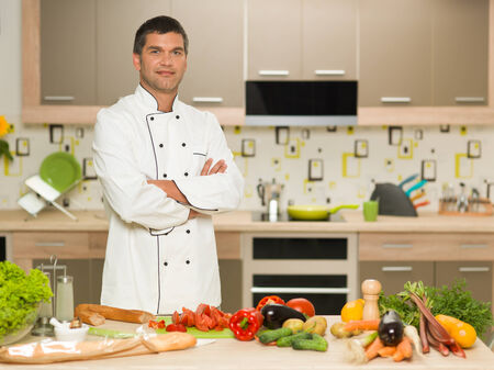 portrait of young caucasian male chef, standing with cut vegetables in front photo