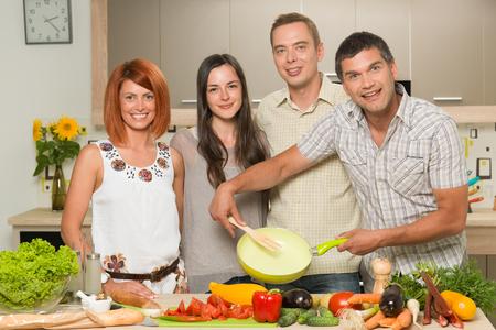 hombre cocinando: vista frontal de las personas caucásicas jóvenes de pie en la cocina, cocinar Foto de archivo