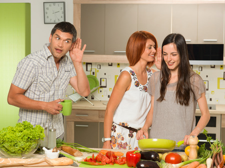 portrait of two beautiful caucasian women standing in kitchen cooking, laughing and whispering something, with one man behing them eavesdropping photo