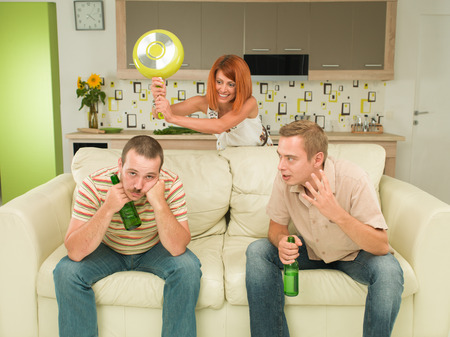 two caucasian men sitting on couch holding beer bottles, having conversation, woman in background trying to hit one of them with frying pan photo