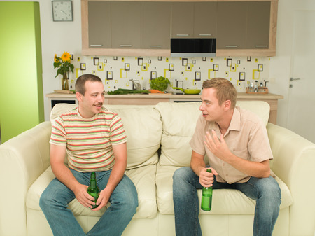 mate drink: two young caucasian men sitting on couch, holding bottles of beers and having conversation