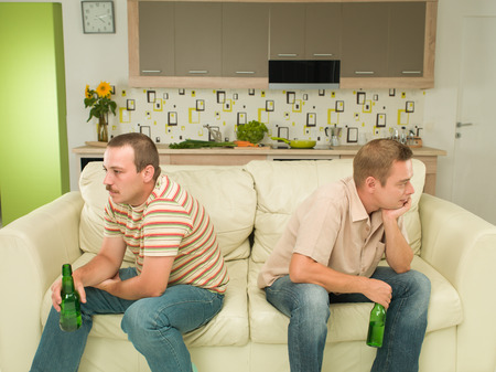 mate drink: two young caucasian men sitting on couch, acting upset Stock Photo