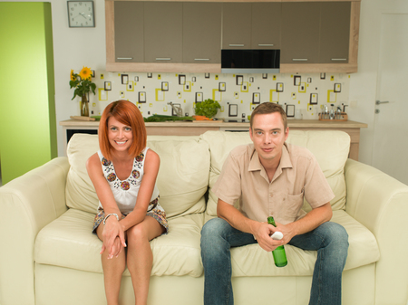 couple couch: young caucasian man and woman sitting on couch watching tv together Stock Photo