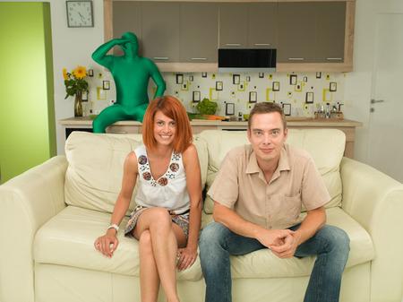 pareja viendo television: joven, caucásico, hombre feliz y mujer que se sienta en el sofá y sonriente, con hombre en el fondo verde que desgasta de cuerpo completo traje sentado mostrador de la cocina