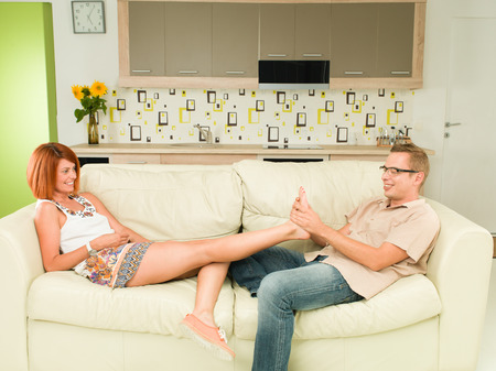 young caucasian happy couple relaxing on sofa, man giving foot masssage to his girlfriend