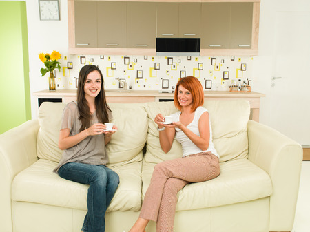 two happy young female friends with coffee cups sitting on sofa and smiling photo