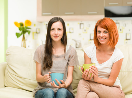 two young caucasian happy girls sitting on sofa, holding mugs of coffee and smiling photo